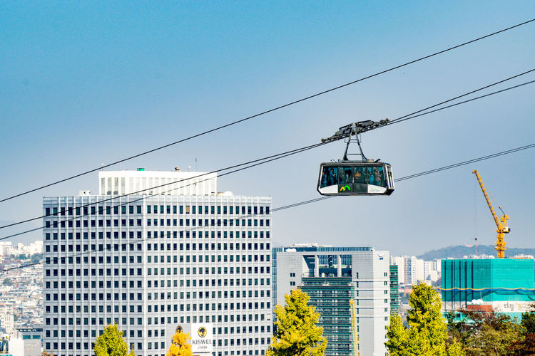 Low angle view of overhead cable car against buildings