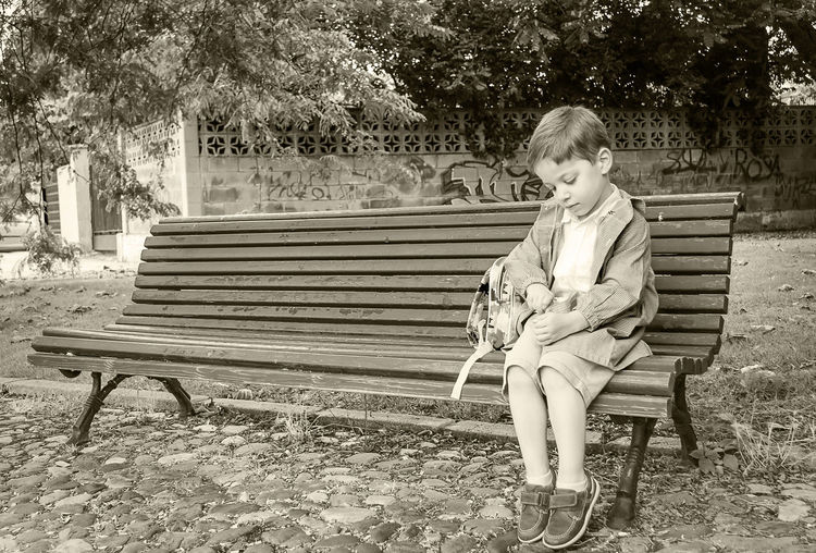 Boy sitting on bench in park