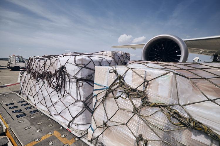Preparation before flight. loading of cargo containers against jet engine of freight airplane.