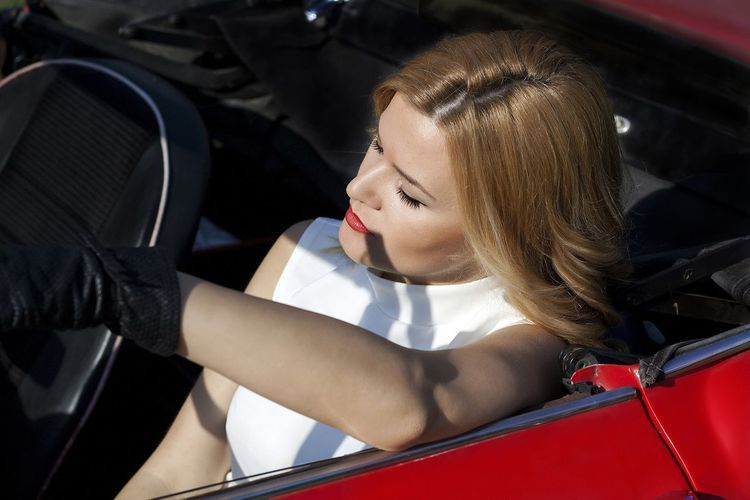 High angle view of fashionable woman sitting in red convertible vintage car on sunny day