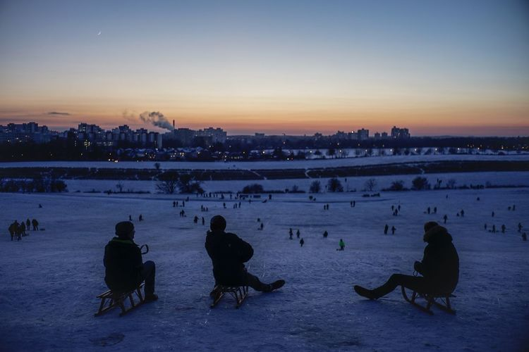 People sitting on snow covered landscape against sky during sunset