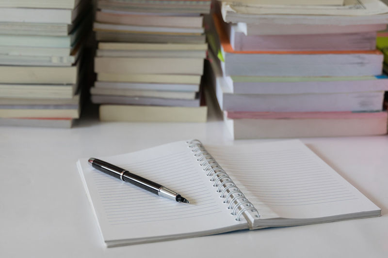 Close-up of pen on open blank book at table
