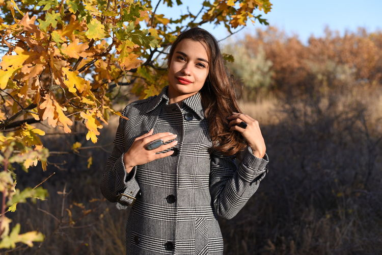 Beautiful young woman standing by tree during autumn