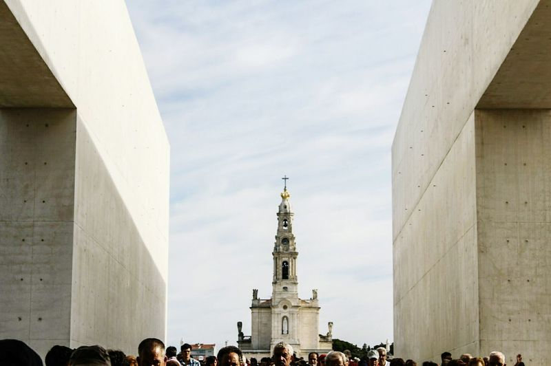Tourists in front of cathedral against sky