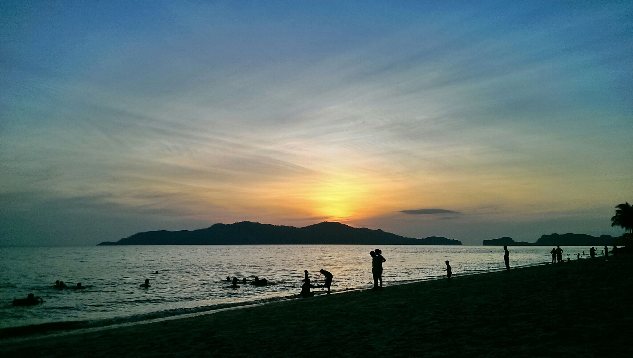 sunset, sea, scenics, water, silhouette, beach, beauty in nature, tranquil scene, sky, tranquility, orange color, shore, nature, mountain, idyllic, cloud - sky, vacations, incidental people, unrecognizable person