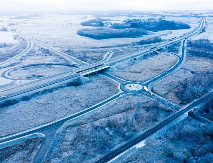 Frozen highway Motorway Freeway Interstate Winter Cold Blue Frozen Ice Icy Lithuania Lietuva Roundabout Traffic Traffic Circle Winter Cold Temperature Blue Road Sunset Backgrounds Sky Landscape Aerial View Elevated Road Highway Two Lane Highway Multiple Lane Highway Viaduct Overpass Empty Road