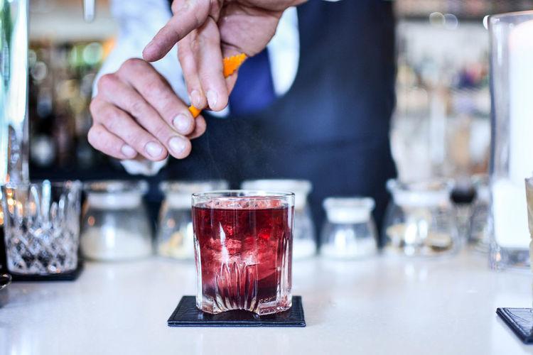 Close-Up Of Bartender Preparing Cocktail At Counter