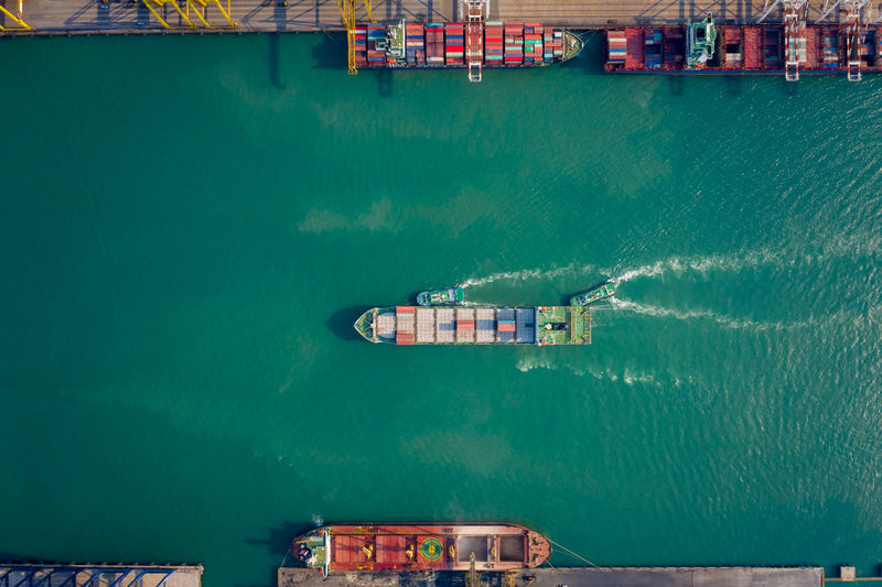 Aerial top view tugboat pushing container ship to quayside for load/unload container via crane