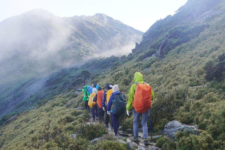 Rear view of people walking towards mountain