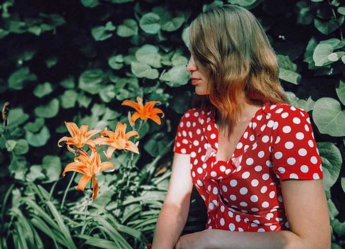 Woman with blond hair sitting by flowers against plants