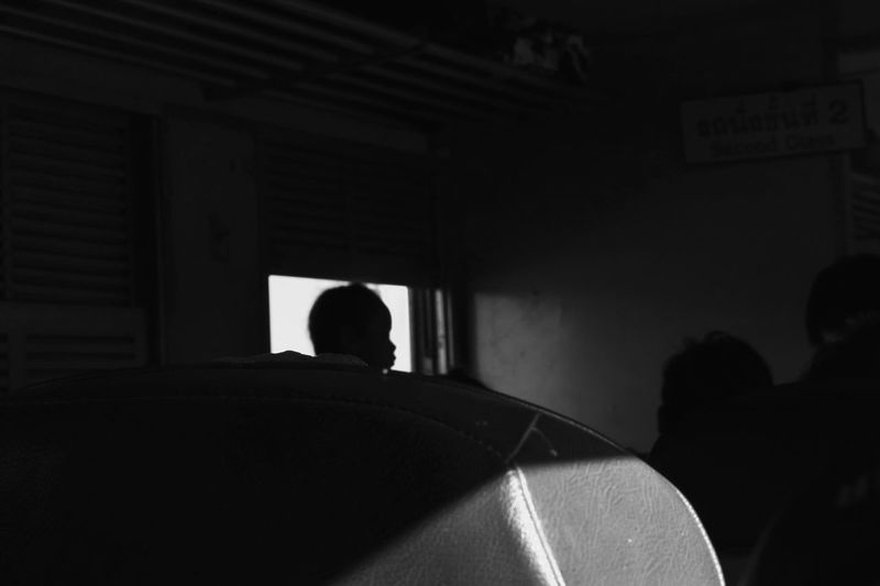 Rear view of silhouette man sitting in bus