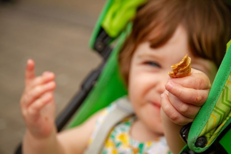 Close-up of baby girl holding food on carriage