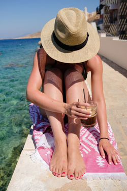 Person with a hat and cold coffee - Aegean, Greece 2018 Aegean Coffee Halki Hat Portrait Of A Woman Beach Clothing Day Greece Hat Ice Coffee Leisure Activity Lifestyles One Person Portrait Real People Shadows Summer Sunbathing Swimwear Water Women