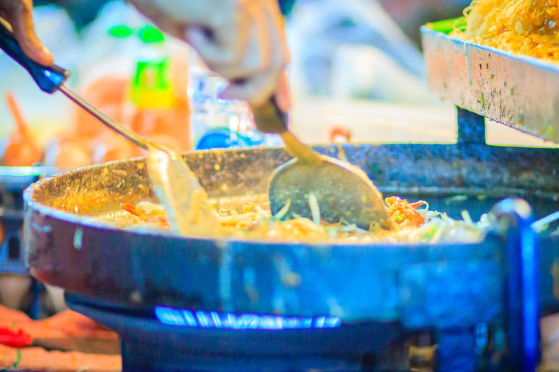 Close up hand of vendor during cooking for Padthai, the original Thai Fried Noodle, stir-fried noodle with shrimp and egg commonly served as a street food popular in Thailand Khao San Rd Khao San Road KhaoSan Khaosan Rd. Khaosandroad Pad Thai Shrimp Pad Thai With Shrimp Tourist Tourist Attraction  Tourists Khao San Khao San Knok Wua Khao San Rd. Khaosan Road Khaosanroad Night Market Night Market In Thailand Night Market, Pad Thai Pad Thai Kung Padthai Padthai Food Padthai Grassnoodle Tourist Destination