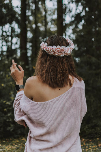 Rear view of woman wearing flowers standing at forest