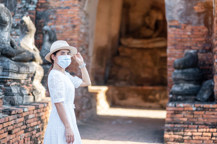 Mid adult woman wearing mask looking away while standing against ancient structure