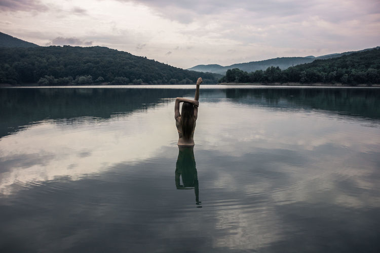 Beautiful young woman bathes in a lake. It stands at the bottom of the waist in the water. Her hair is loose. In the photo one person. The water in the lake is a calm, peaceful landscape. In the background, mountains with green vegetation on them. In the water reflection of the earth and sky with clouds. Alone Fashion Arms Raised Beauty In Nature Cloud - Sky Hairstyle Human Arm Lake Leisure Activity Lifestyles Mountain Nature One Person Only Women Outdoors Real People Rear View Reflection Scenics - Nature Sky Tranquil Scene Tranquility Water Waterfront Women 10 The Photojournalist - 2018 EyeEm Awards The Great Outdoors - 2018 EyeEm Awards The Still Life Photographer - 2018 EyeEm Awards The Traveler - 2018 EyeEm Awards The Portraitist - 2018 EyeEm Awards The Creative - 2018 EyeEm Awards The Fashion Photographer - 2018 EyeEm Awards The Street Photographer - 2018 EyeEm Awards Love Is Love