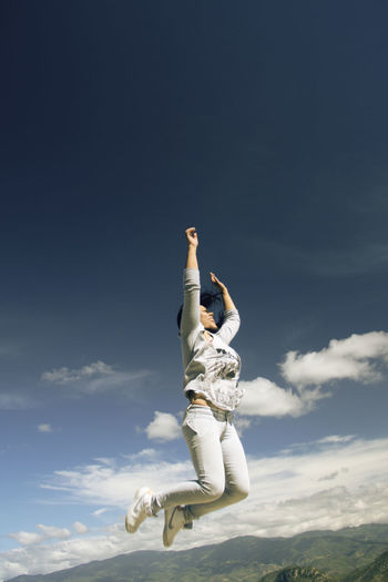 LOW ANGLE VIEW OF WOMAN JUMPING AGAINST CLEAR SKY