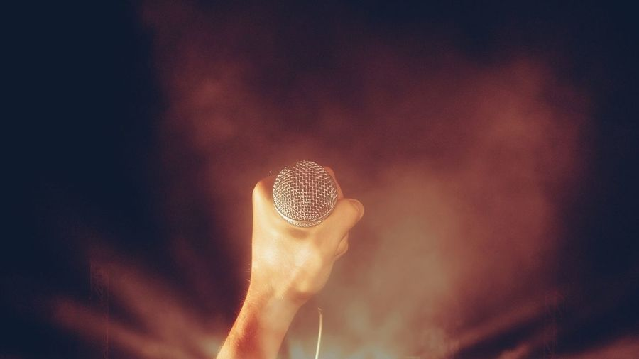 Close-Up Of Human Hand Holding Microphone At Night