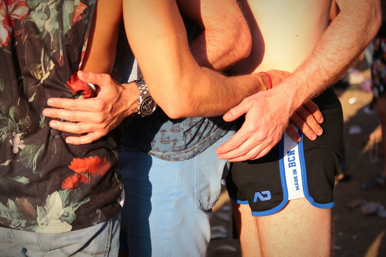 Midsection of men with arms around