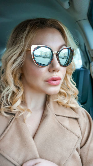 Woman in car wearing sunglasses with reflection