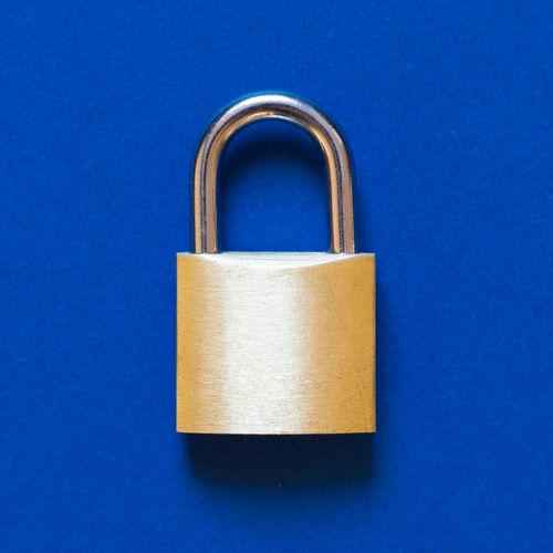 Directly above shot of padlock on blue background