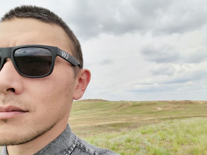 Portrait of young man wearing sunglasses on field against sky