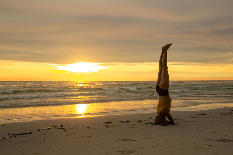 Woman doing headstand at beach against sky during sunset