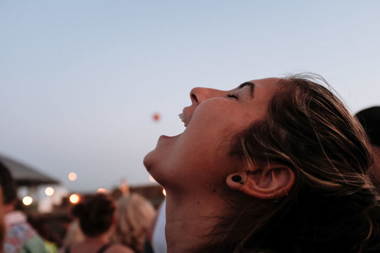 Laughing young woman in city against sky