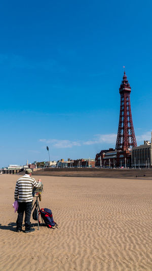 A painter at the sandy beach with the Blackpool tower at the background Adult Architecture Beach Blackpool Blue Casual Clothing Day Full Length Lifestyles Low Tide One Person Outdoors Painter People Real People Rear View Sandy Seaside Resort Sky Standing Tourism Tower Travel Destinations