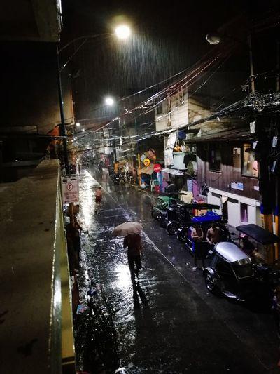 Wet walking on illuminated street during rainy season at night