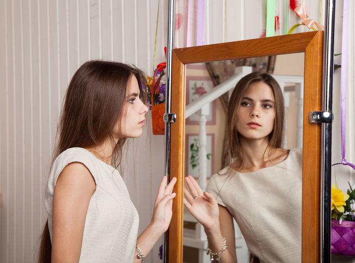 Beautiful Woman Looking In Mirror At Home