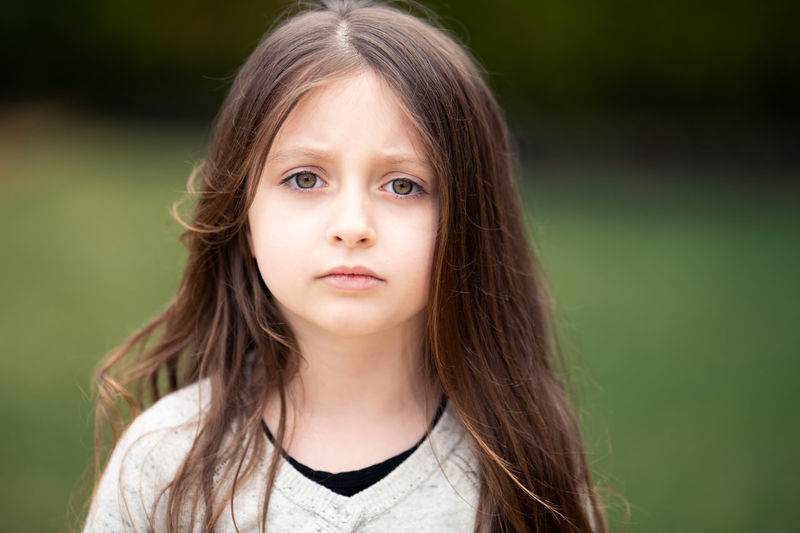 Close-up portrait of cute girl with hazel eyes in park