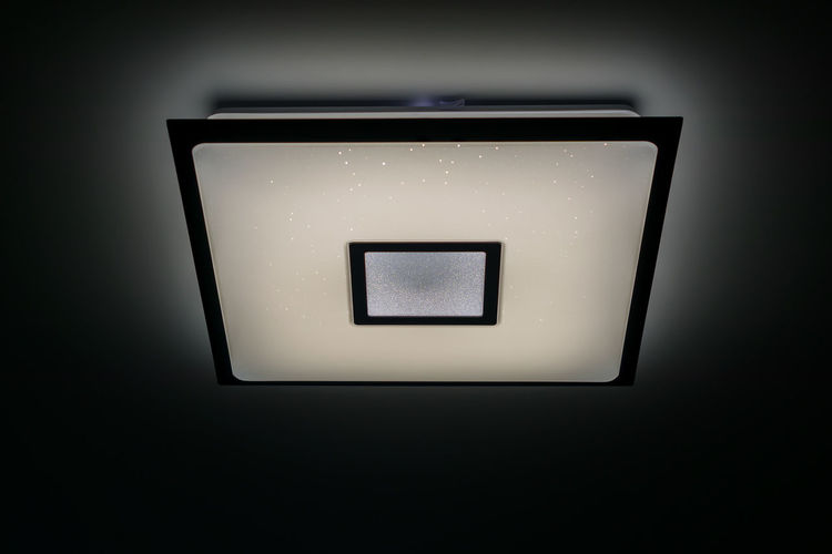Directly below shot of illuminated electric lamp against black background