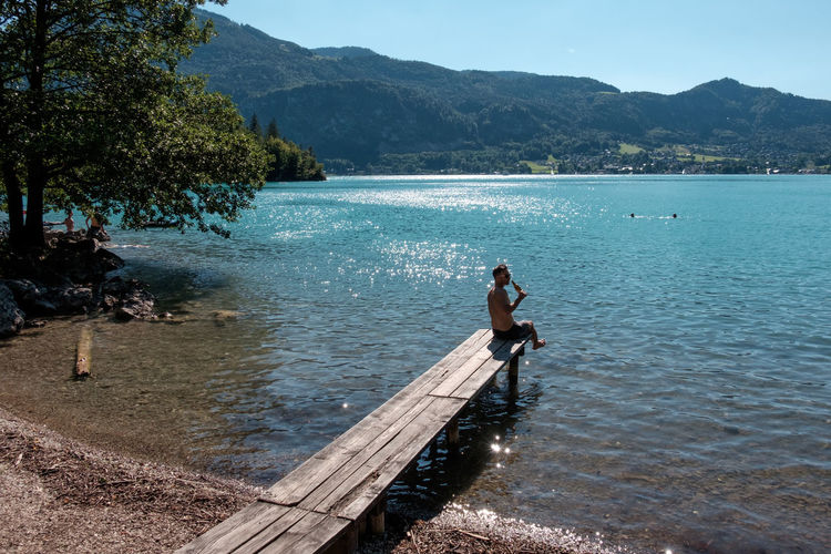 Austria Holiday Man Salzkammergut Summertime Swimming Beachday Beauty In Nature Crisp Day Drink Jetty Lake Landscape Lush Mountain Nature Outdoors Real People Scenics Sky Summer Water Wolfgangsee Young Adult