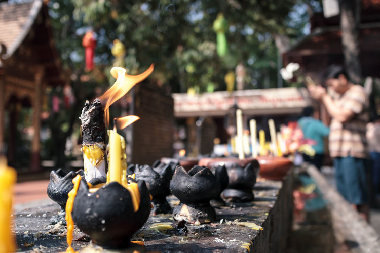 Burning candles in temple against building