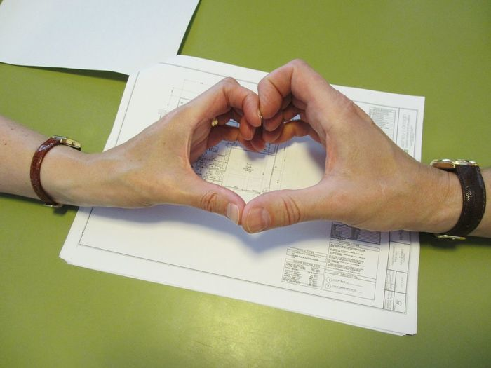 Cropped image of couple making heart from hands over blueprint on table