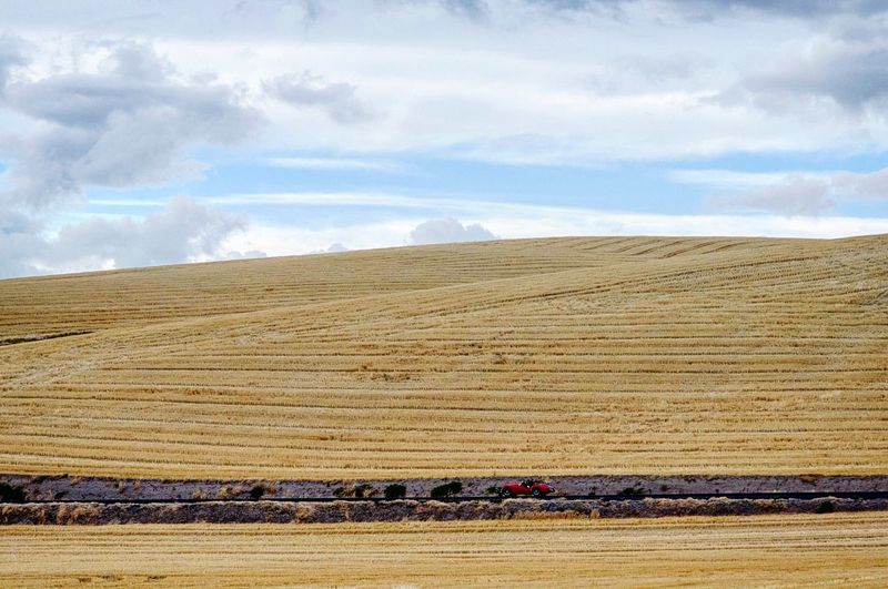View Of Harvested Rolling Landscape Against Cloudy Sky
