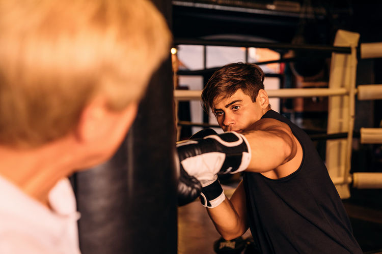 Instructor standing by boxer punching bag in boxing ring