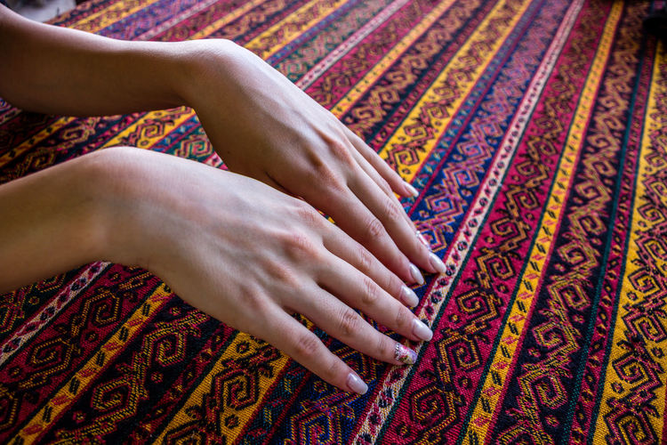 Cropped hands of woman touching patterned fabric