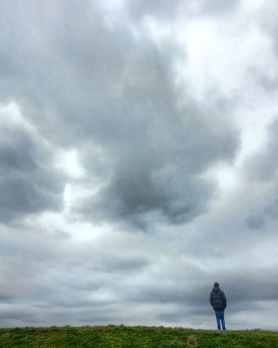 Single man standing in solitude against a grey wall of dark clouds Beauty In Nature Casual Clothing Cloud - Sky Day Field Full Length Grass Landscape Leisure Activity Lifestyles Men Nature One Man Only One Person Outdoors People Real People Rear View Sky Standing Walking