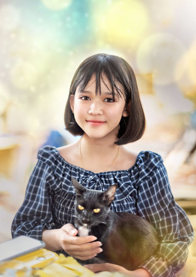 Portrait of smiling woman with cat