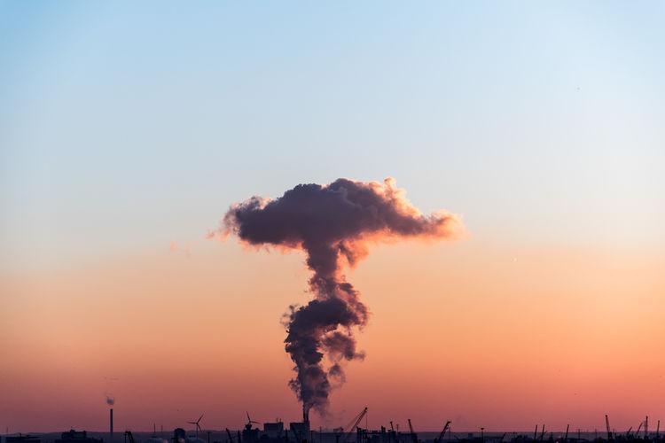 Smoke emitting from chimney against sky at sunset