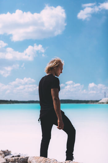 Curly blond man dressed in all black. posing on the sea beach. Impressive shoot, trendy hairstyle. Summer time. Adult Beach Beauty In Nature Casual Clothing Cloud - Sky Contemplation Full Length Hairstyle Horizon Over Water Land Leisure Activity Lifestyles Nature One Person Outdoors Real People Sea Sky Standing Water Young Adult