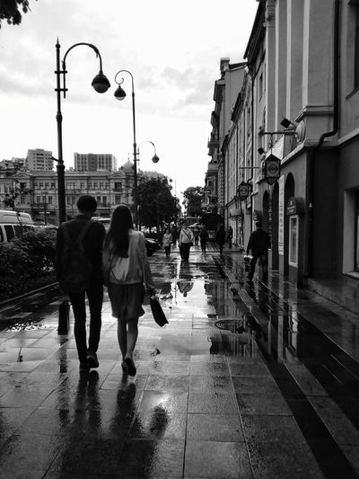 People on the street after the rain Wet Street Walking Adult Togetherness Rear View City People Men Water Sky Day Adults Only Young Adult Outdoors Full Length After The Rain Lamp Posts Black And White Black & White Black And White Friday
