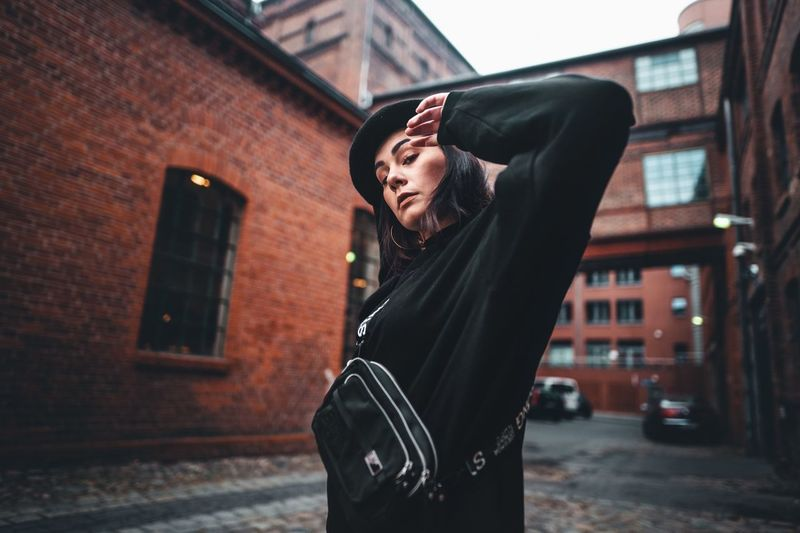 One Person Young Adult Building Exterior Architecture Standing Built Structure Focus On Foreground Young Women Real People Lifestyles City Leisure Activity Front View Three Quarter Length Building Day Casual Clothing Looking Outdoors Brick Beautiful Woman Hairstyle