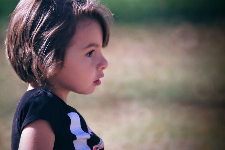 Close-up of cute girl looking away in playground