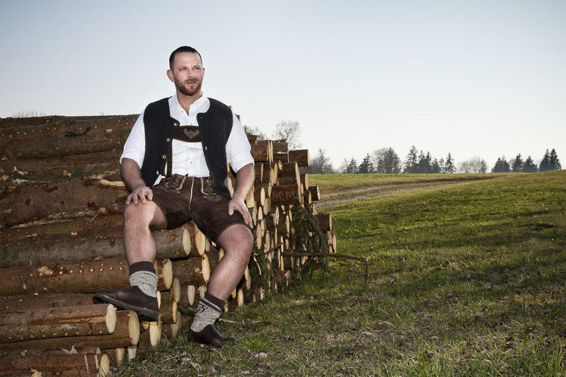 Man Sitting On Logs At Field Against Clear Sky