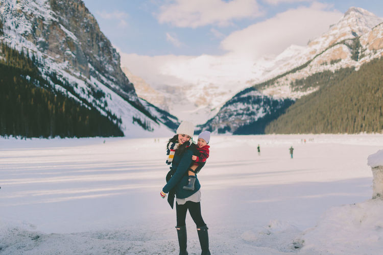 Mother Piggybacking Son On Snow Against Mountains During Winter