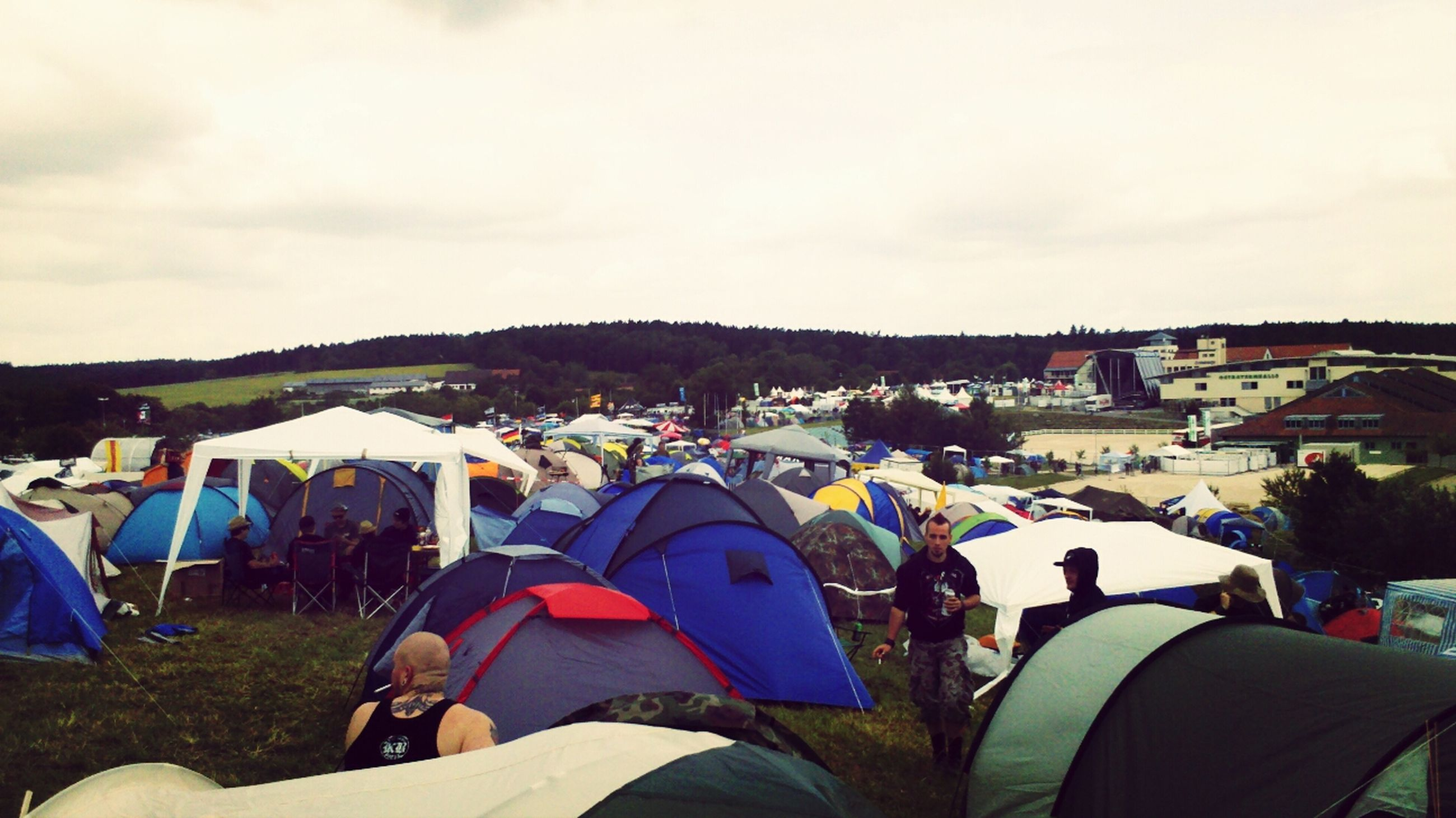 sky, building exterior, men, tent, built structure, architecture, lifestyles, large group of people, leisure activity, person, mountain, outdoors, house, cloud - sky, day, landscape, cloud, panoramic, field